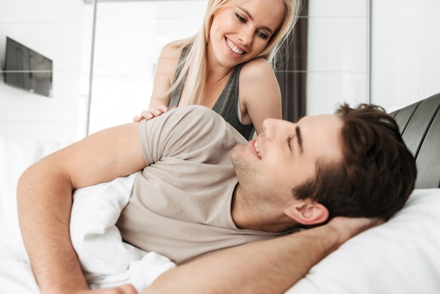 Young lady looking at her husband while lying in bed