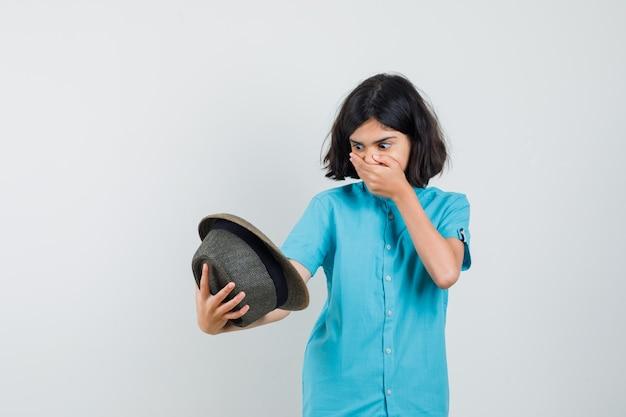 青いシャツの帽子の中を見て、怖がって見える若い女性