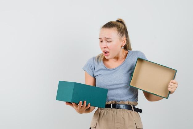 Tシャツとズボンのプレゼントボックスを見て、ダウンキャストを見ている若い女性