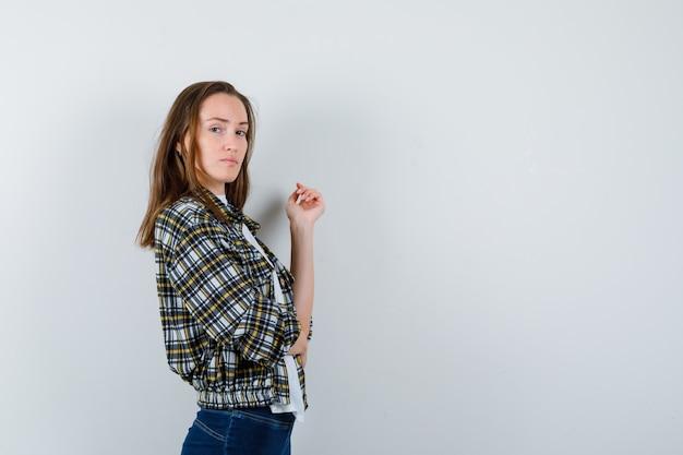 Giovane donna che osserva sopra la spalla mentre posa in maglietta, giacca, jeans e sembra sicura. vista frontale.
