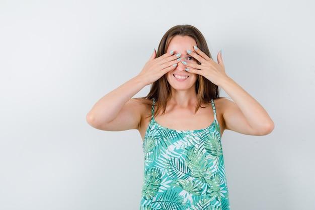 블라우스를 입은 손가락을 통해 보고 귀엽고 앞모습을 보고 있는 젊은 여성.
