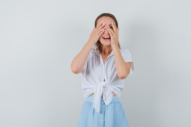 Молодая дама смотрит сквозь пальцы в блузке и юбке и радуется