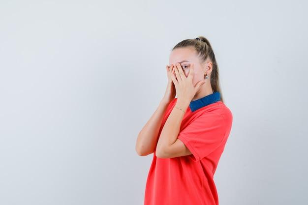 Молодая дама смотрит сквозь пальцы в футболке и выглядит спокойной