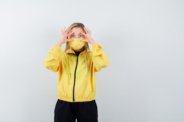 Giovane donna che guarda attraverso le dita in tuta da ginnastica, maschera e sembra stupita. vista frontale.