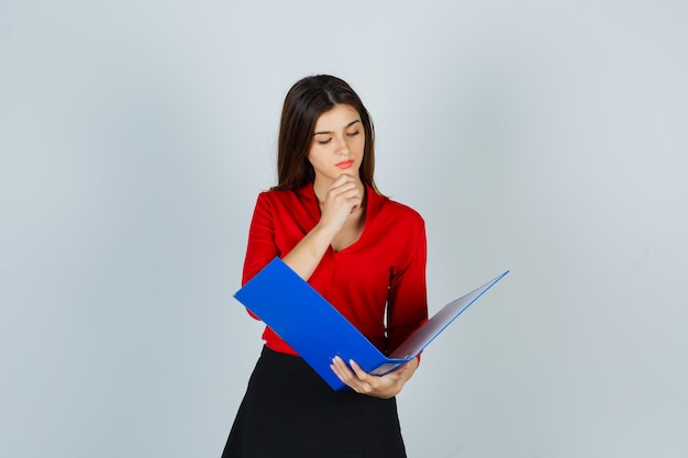 Young lady looking through folder in red blouse, skirt and looking focused