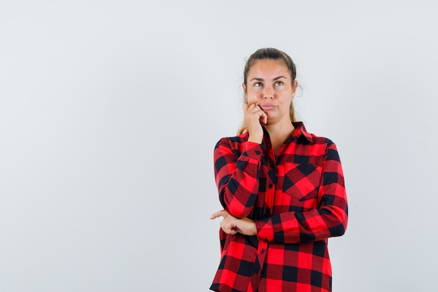 Young lady looking up in checked shirt and looking thoughtful