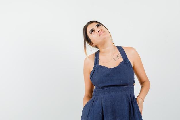 Giovane donna che guarda in alto in abito e sembra concentrata