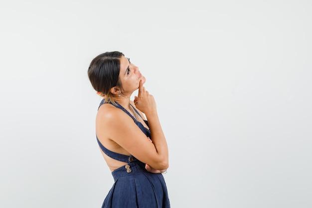 Giovane donna che alza lo sguardo in abito e sembra pensierosa