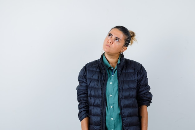Young lady looking up in shirt, puffer jacket and looking thoughtful , front view.