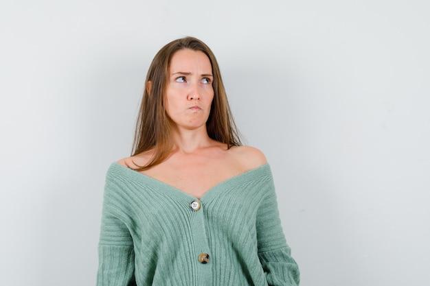 Giovane donna che osserva in su mentre pensa in cardigan di lana e sembra turbata, vista frontale.