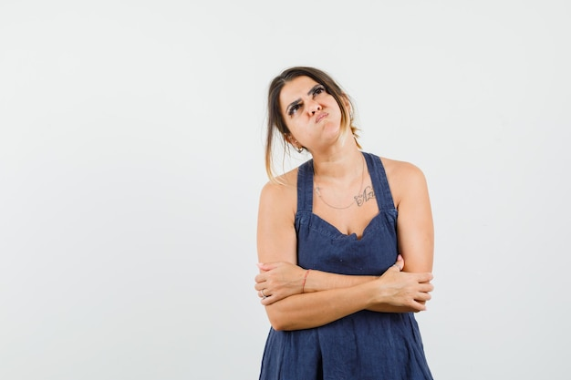 Giovane donna che guarda in alto con le braccia incrociate in abito e sembra cupa