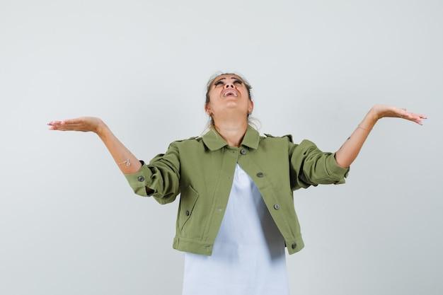 Giovane signora che osserva in su con le braccia aperte in rivestimento della maglietta e che sembra allegra