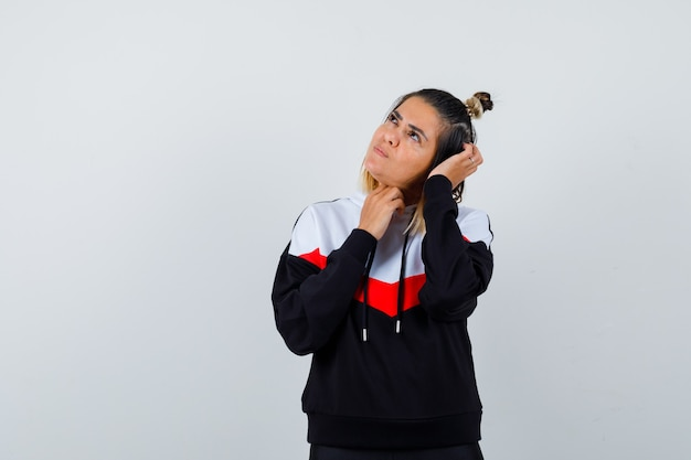パーカーのセーターで頭を掻きながら上向きに見ていると思慮深く見える若い女性
