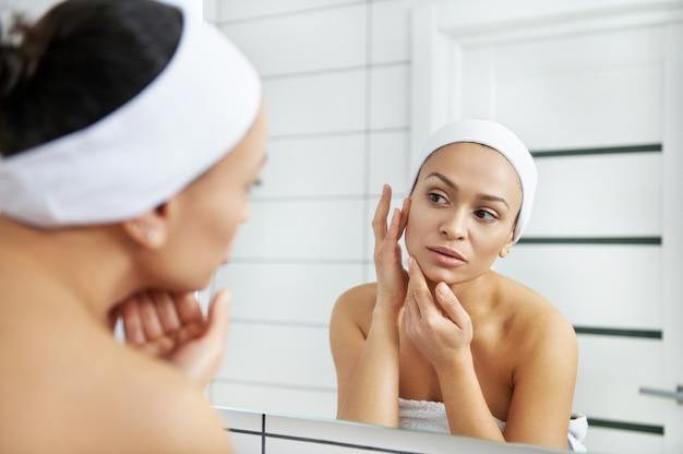 若い女性は、保湿された柔らかく健康的な敏感肌に触れるバスルームの鏡を見てください。朝の水分補給スパ美容ルーチン。
