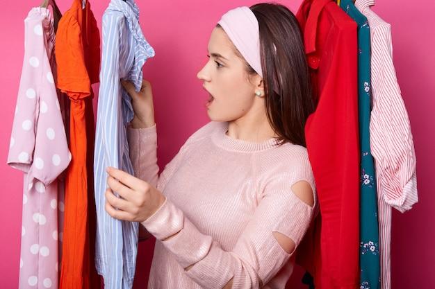 Молодая леди смотрит на ценники в магазине одежды. брюнетка женщина находит пятно на новой блузке в выставочном зале. дорогая одежда