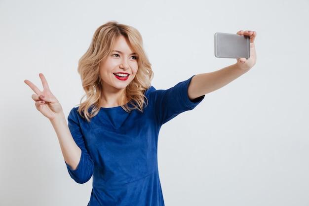 La giovane signora fa il selfie con il gesto di pace per telefono