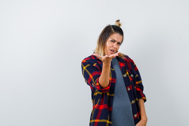 캐주얼 체크 셔츠를 입고 질문 제스처를 하고 사려깊은 정면을 바라보는 젊은 여성.