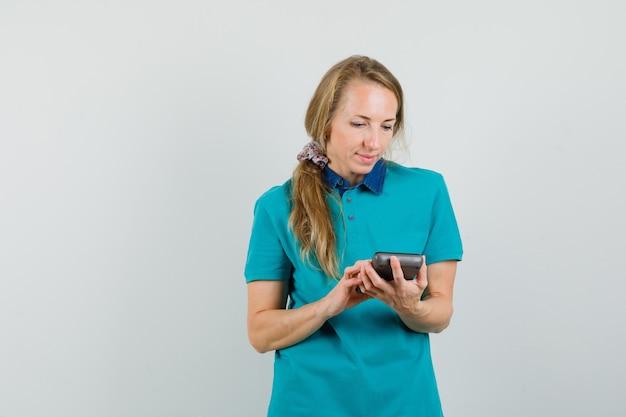 Giovane donna che fa il calcolo sulla calcolatrice in maglietta e sembra occupata.