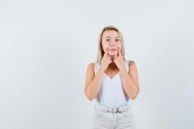 白いブラウスで偽の笑顔を作る若い女性 無料写真