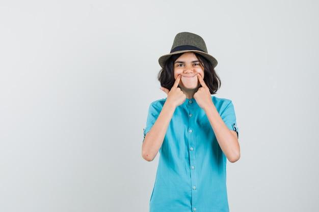 青いシャツを着た指で偽の笑顔を作り、前向きに見える若い女性