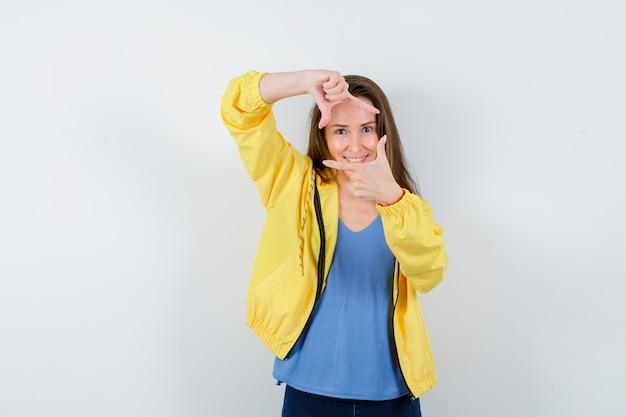 若い女性がtシャツでフレームジェスチャーを作成し、自信を持って、正面図を探しています。