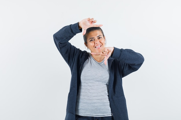 Tシャツでフレームジェスチャーを作る若い女性