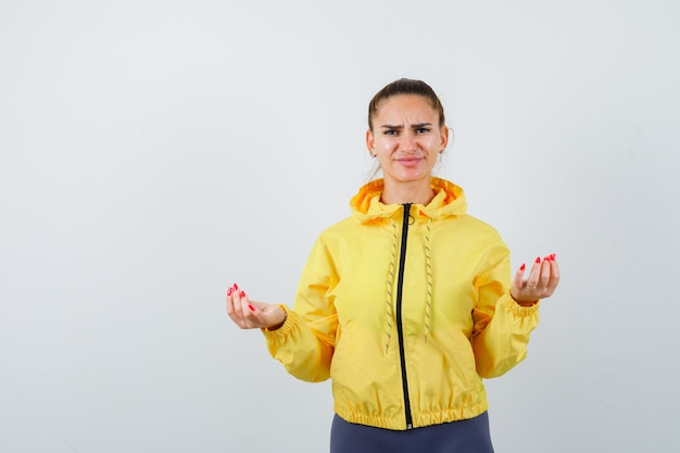 Young lady making money gesture in yellow jacket and looking displeased , front view.