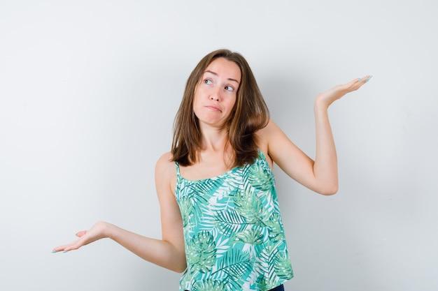 ブラウスで体重計のジェスチャーをし、躊躇している若い女性、正面図。