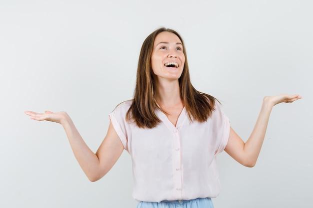 Девушка делает весы жест в футболке, юбке и выглядит счастливым, вид спереди.