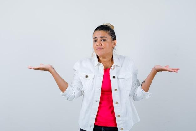 Tシャツ、白いジャケットで体重計のジェスチャーをし、注意深く見ている若い女性。正面図。