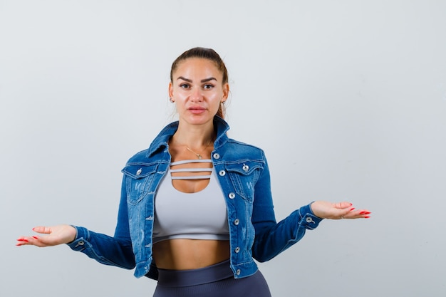 上に体重計のジェスチャーをしている若い女性、デニムジャケットと困惑しているように見える、正面図。