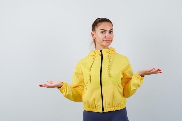 黄色いジャケットで体重計のジェスチャーをし、優柔不断に見える若い女性、正面図。