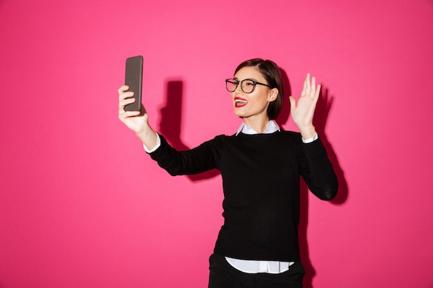 Young lady making selfie on smartphone isolated