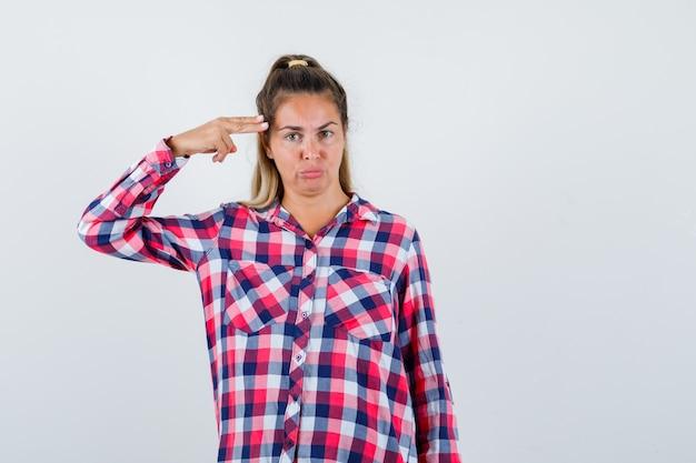 Giovane donna che fa gesto di suicidio in camicia a quadri e guardando fiducioso, vista frontale.