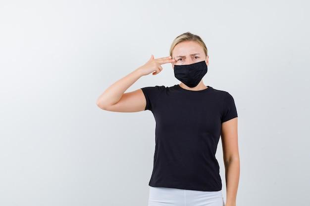 Giovane donna che fa un gesto suicida in maglietta, pantaloni, maschera medica e sembra senza speranza