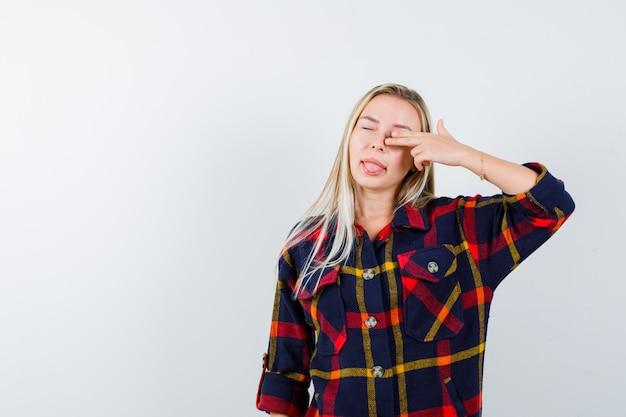 Молодая дама делает самоубийственный жест, высунув язык в клетчатую рубашку и выглядит смешно. передний план.