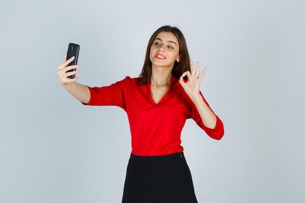 Giovane signora che fa videochiamata mentre mostra il gesto giusto in camicetta rossa