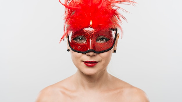 Young lady in mask with red feathers