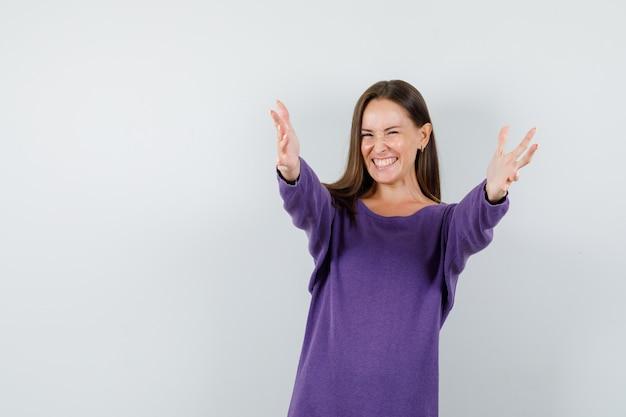 Молодая дама в фиолетовой рубашке раскрывает объятия и выглядит счастливой. передний план.