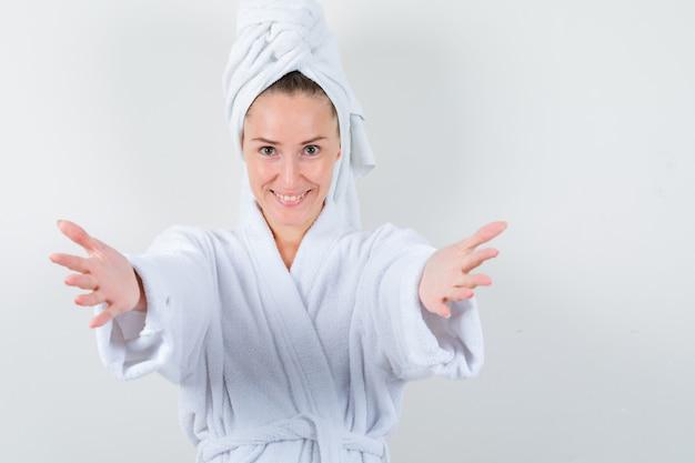 흰색 목욕 가운, 수건에 포옹을 위해 팔을 열고 예쁜, 전면보기를 찾고 젊은 아가씨.