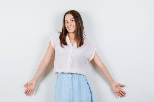 Молодая дама широко раскрывает объятия в футболке, юбке и выглядит веселой, вид спереди.