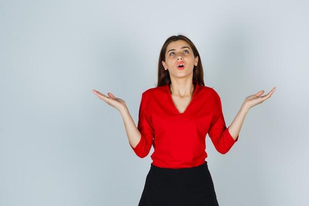 Giovane donna che apre i palmi per pregare in camicetta rossa, gonna e guardare speranzoso