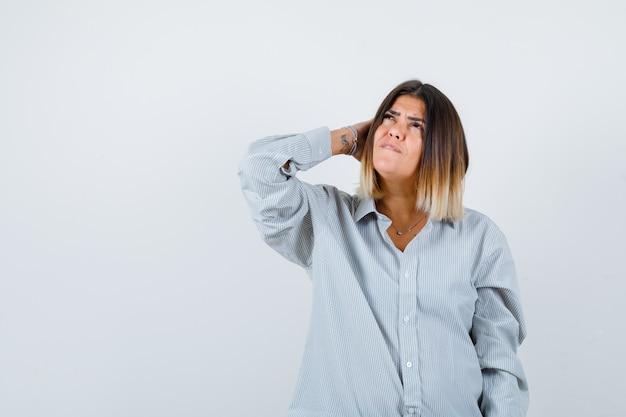 Giovane donna in camicia oversize che tiene la mano sulla testa e sembra premurosa, vista frontale.