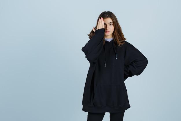 Giovane donna in felpa con cappuccio oversize, pantaloni tenendo la mano sugli occhi e guardando fiducioso, vista frontale.