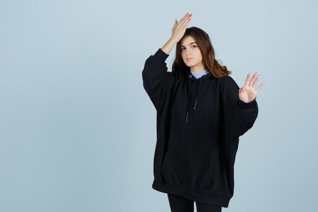 Giovane donna in felpa con cappuccio oversize, pantaloni che tengono la mano sulla fronte mentre mostra il palmo e sembra smemorata, vista frontale.
