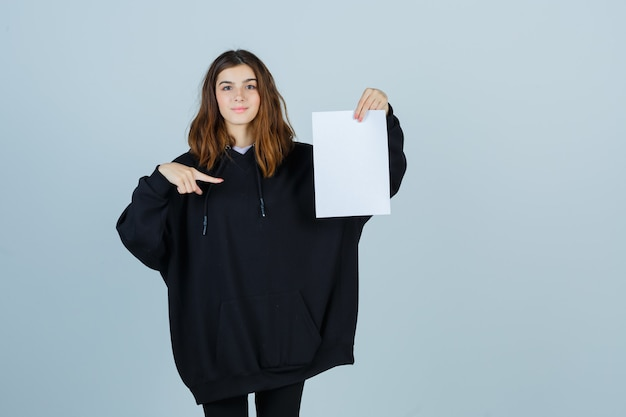 Young lady in oversized hoodie, pants pointing paper while holding and looking confident , front view.