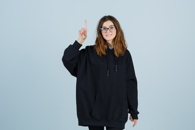 Giovane donna in felpa con cappuccio oversize, pantaloni rivolti verso l'alto e verso il basso e felice, vista frontale.