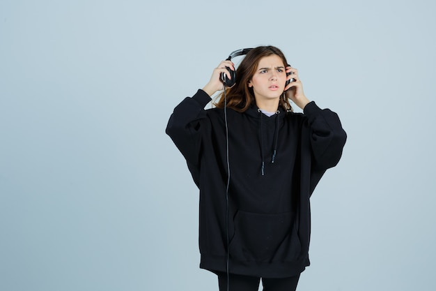 Young lady in oversized hoodie, pants taking of handphones and looking puzzled , front view.