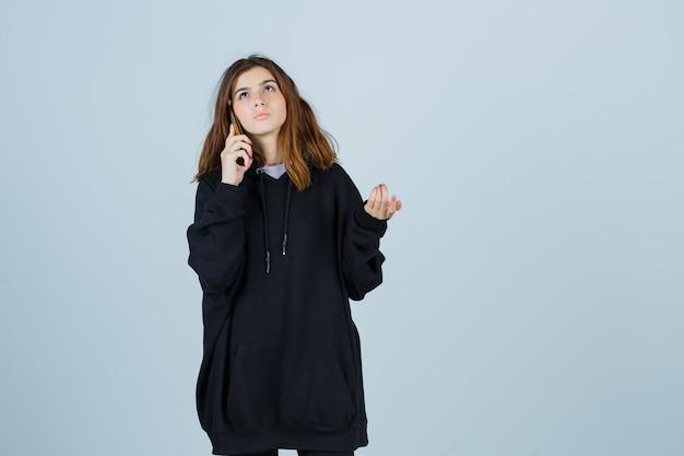 Giovane donna in felpa con cappuccio oversize, pantaloni parlando al cellulare mentre guarda in alto e guarda pensierosa, vista frontale.