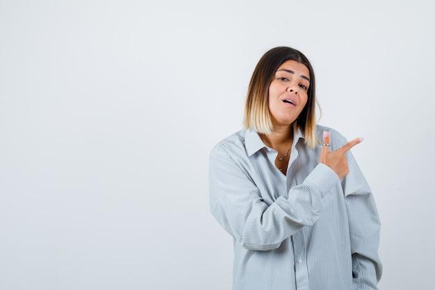 Giovane donna in camicia oversize che punta verso il lato destro e sembra perplessa, vista frontale.